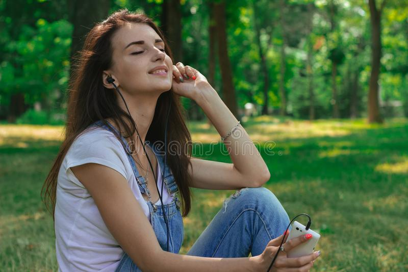 Portrait of young pretty brunette who closed her eyes and listens to music with headphones royalty free stock photography