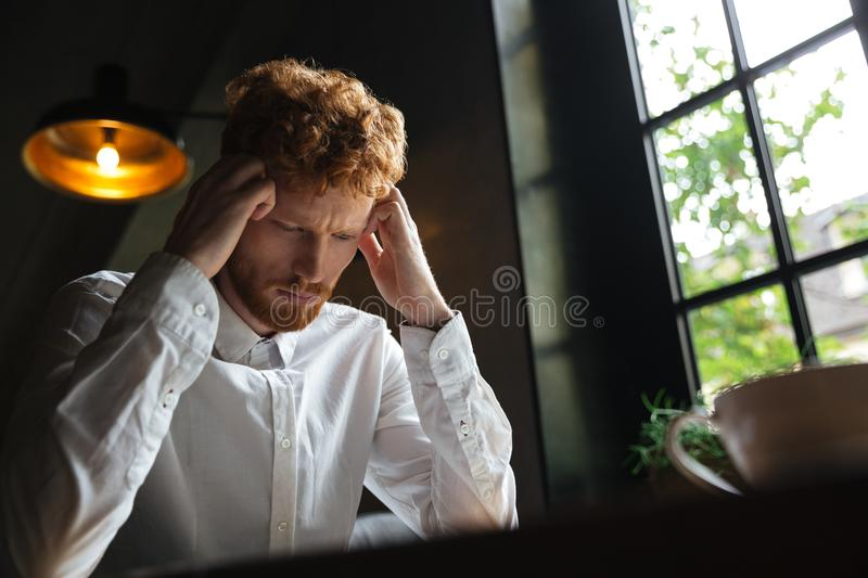 Close-up portrait of young readhead bearded overworked man in white shirt touching his head while sitting at office royalty free stock photos