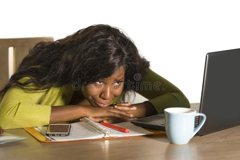 Close up portrait of young sad depressed black afro American business woman crying while working at office computer desk feeling h. Close up portrait of young royalty free stock photography