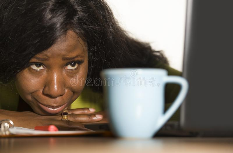 Close up portrait of young sad and depressed black afro American business woman crying while working at office computer desk feeli stock photo