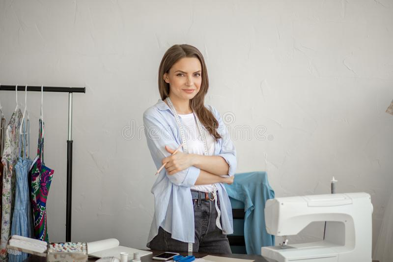 Close-up portrait of young seamstress or dressmaker a her workplace. royalty free stock photos