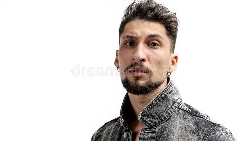 Close up portrait of young serious bearded man in denim shirt that looking at the camera isolated over white background stock photography
