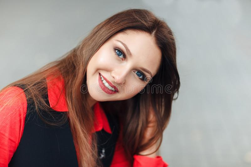 Close-up Portrait of young smiling woman looking at camera, smiling. Attractive girl with long hair sitting on steps an throwing u royalty free stock photography