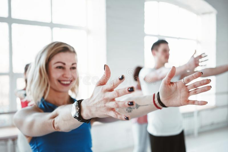 Close-up portrait of young sporty woman doing yoga exercise indoor class together with her friends. Blurred background royalty free stock images