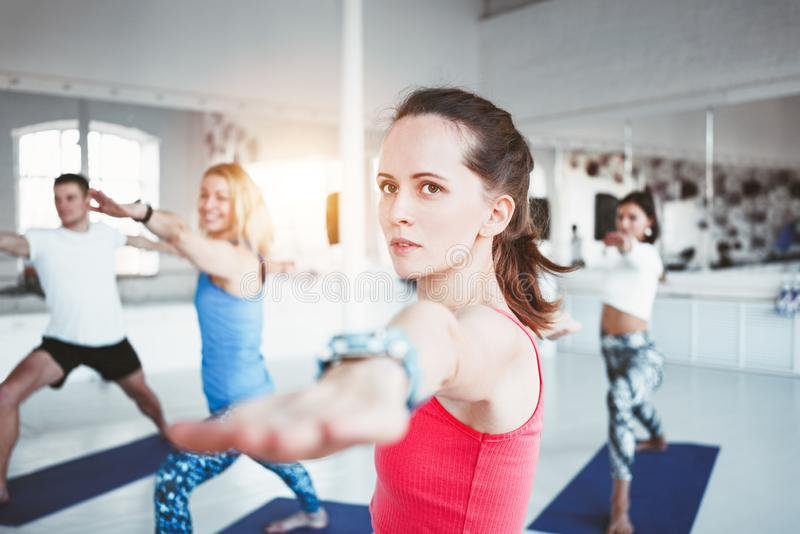 Close-up portrait of young sporty woman doing yoga exercise indoor class together with her friends. Blurred background stock photo