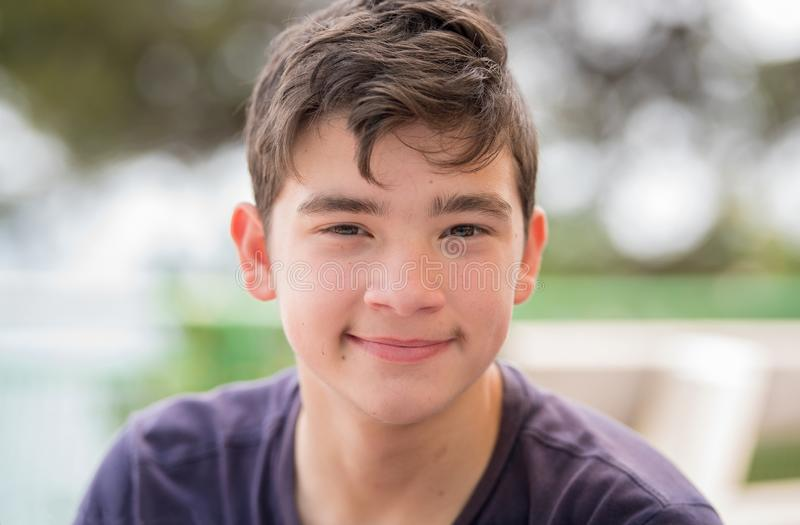 Close up portrait of a young teenager man looking at camera wit stock photo