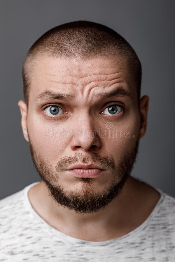 Portrait of a young wary man. Close-up portrait of a young wary man on a gray background stock image