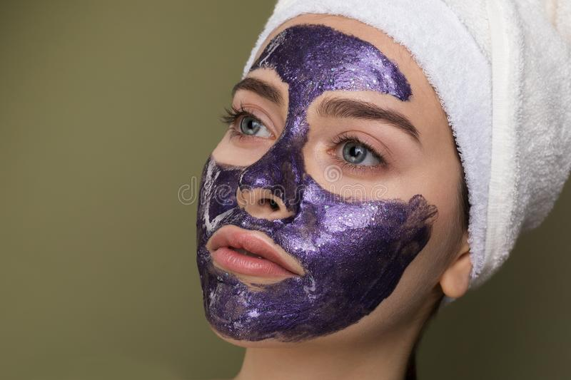 Close up portrait of young woman with blue eyes with towel on her head. Close up portrait of young woman with towel on her head after shower apply purple royalty free stock image