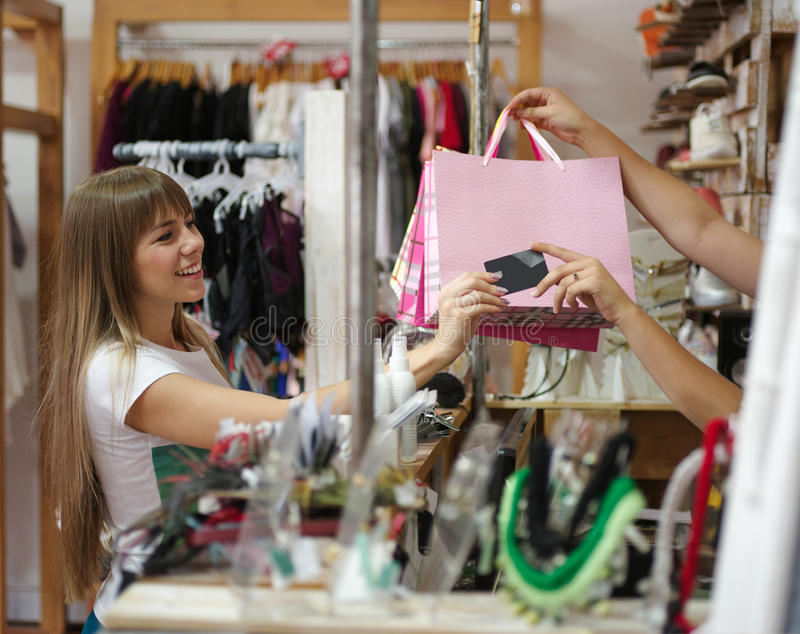 A satisfied woman standing in the clothing store and paying for her purchases. A shopaholic on a blurred background royalty free stock image
