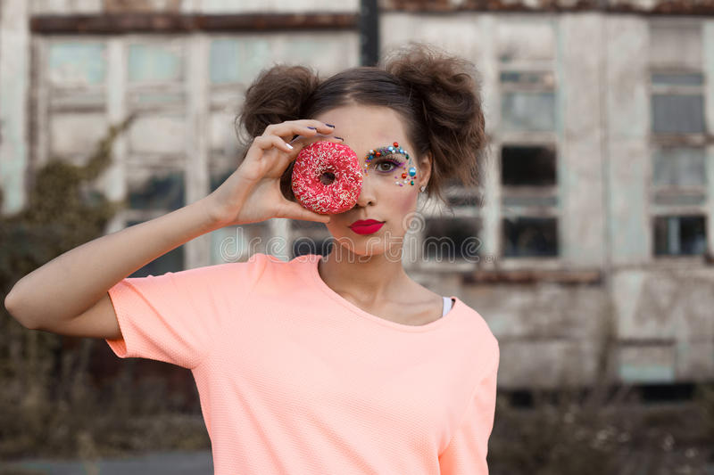 Close up portrait of young woman covering her eyes with donuts on white background.Beauty fashion model girl taking sweets and col royalty free stock photos