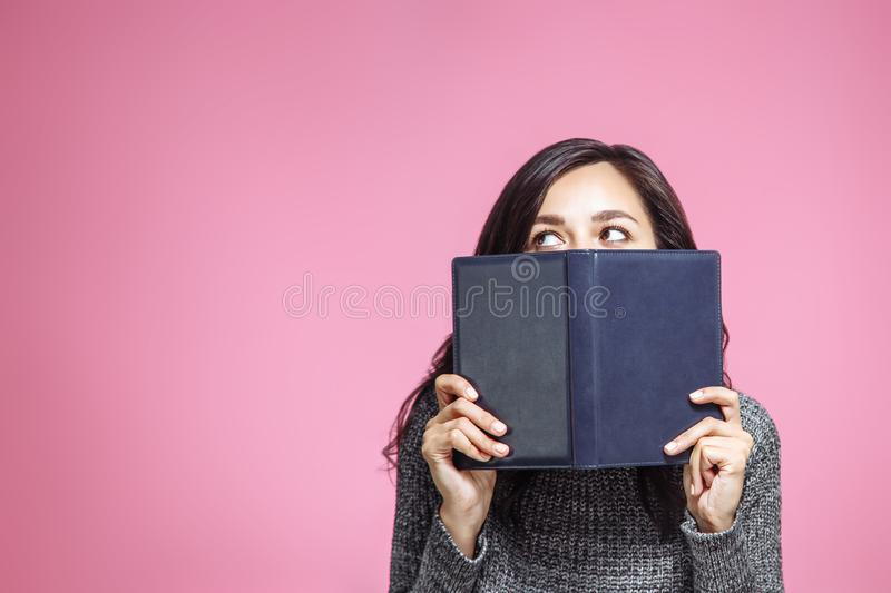 Close up portrait of a young woman covering her mouth with book and looking away isolated on the pink background.  stock photo
