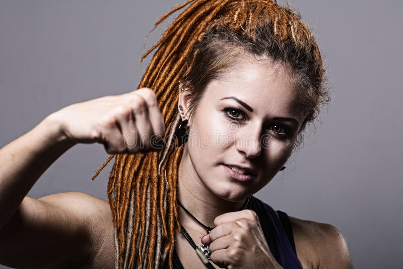 Close-up portrait young woman with dreadlocks in a fighting stan stock image
