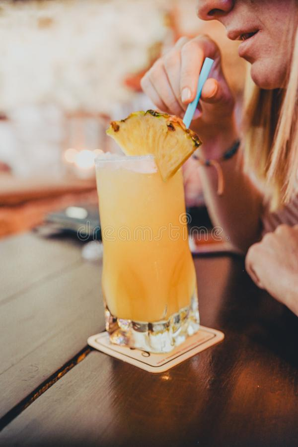 Close up portrait of young woman drinking a pina colada cocktail stock images