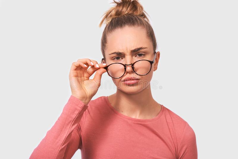 Close up portrait of young woman frowning puzzled teacher looking serious. Beautiful female woman in eyewear looking at camera. stock image
