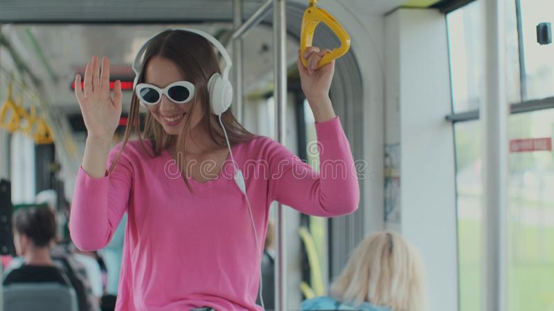 Close-up portrait of a young woman with headphones standing in the modern tram. A woman in glasses listens to music in a. Tram royalty free stock images