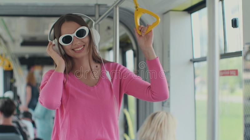 Close-up portrait of a young woman with headphones standing in the modern tram. A woman in glasses listens to music in a. Tram royalty free stock photography