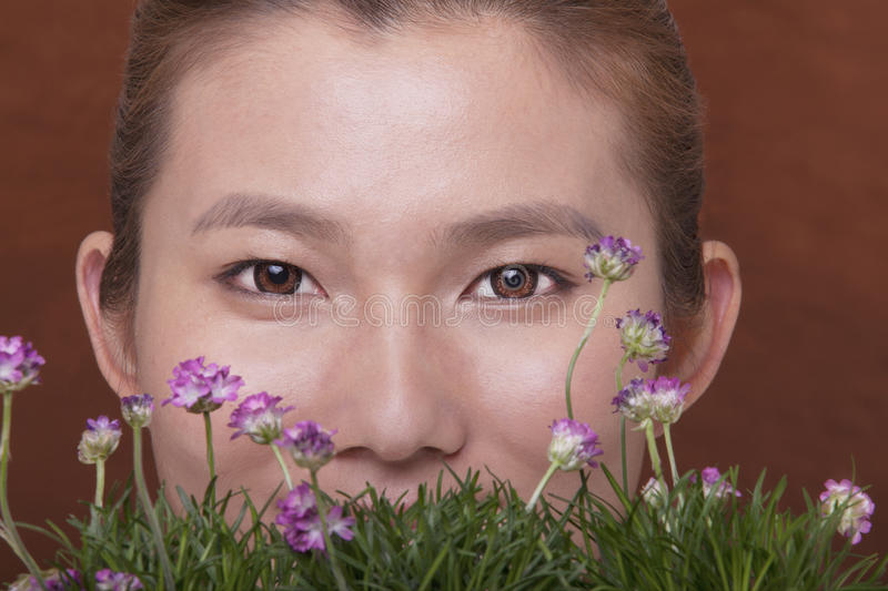 Close- up portrait of young woman with her face behind some flowers and grass, studio shot stock photo