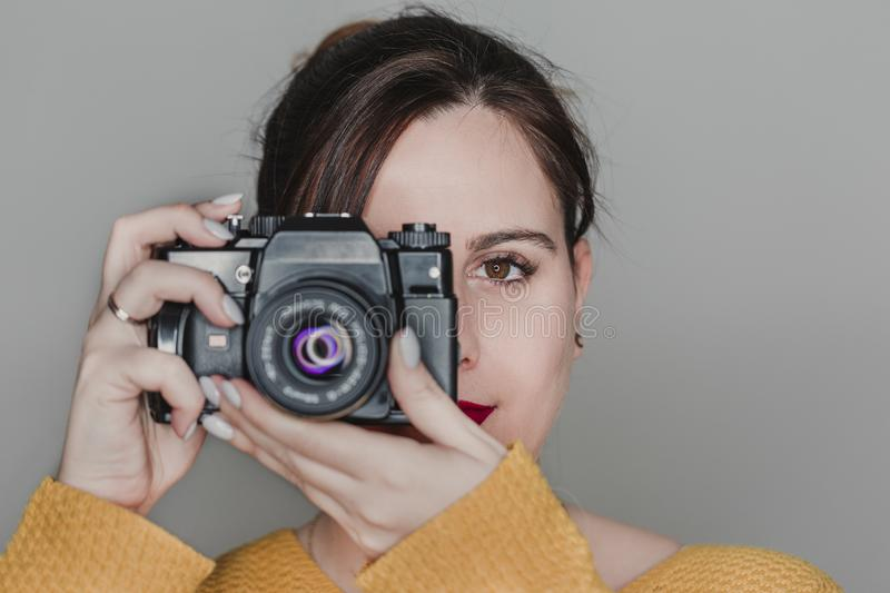 Close up portrait of a young woman holding a camera. Photography concept stock image