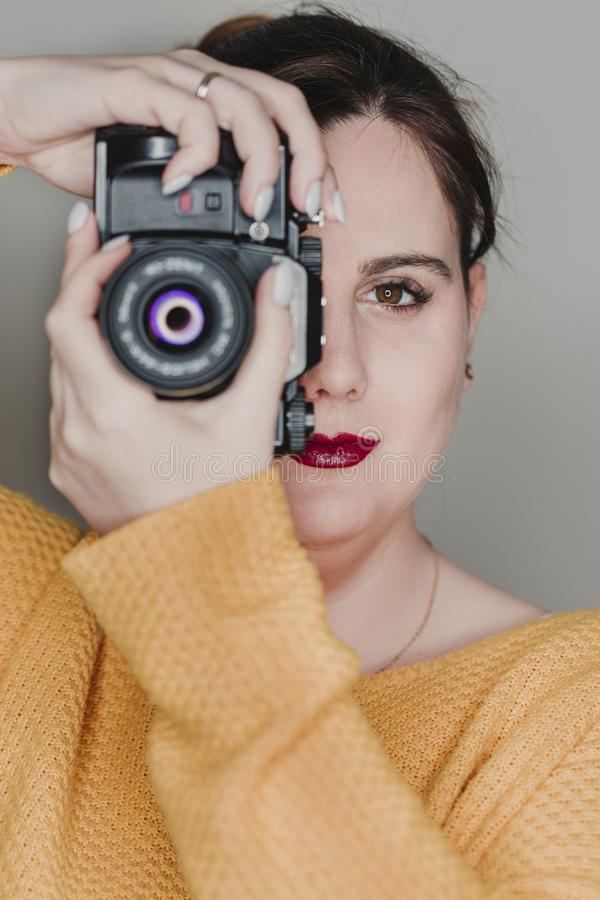 Close up portrait of a young woman holding a camera. Photography concept royalty free stock photos
