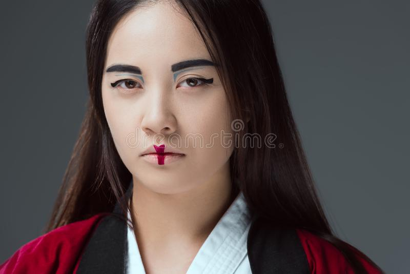 Close-up portrait of young woman with makeup wearing kimono and looking at camera. Isolated on grey stock photo