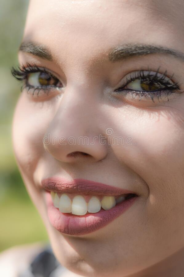 Close up portrait of a young woman outside with trees shadows on the face. Positive girl having fun outside in a sunny day royalty free stock images