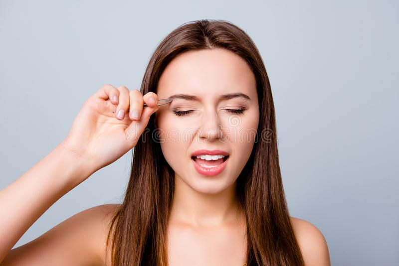 Close up portrait of young woman plucking eyebrows with tweezers stock image