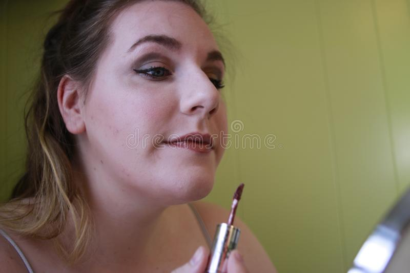 Close up Portrait of Young Woman With Red Lips. Beautiful Woman Doing Daily Makeup. Lipstick applying royalty free stock photos