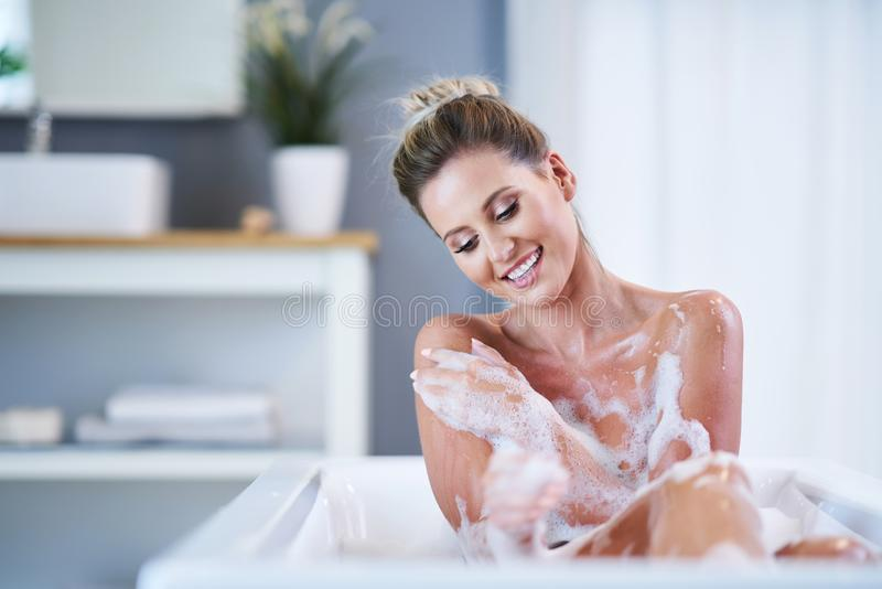 Close-up portrait of a young woman relaxing in the bathtube. Portrait of a young woman relaxing in the bathtube royalty free stock photography