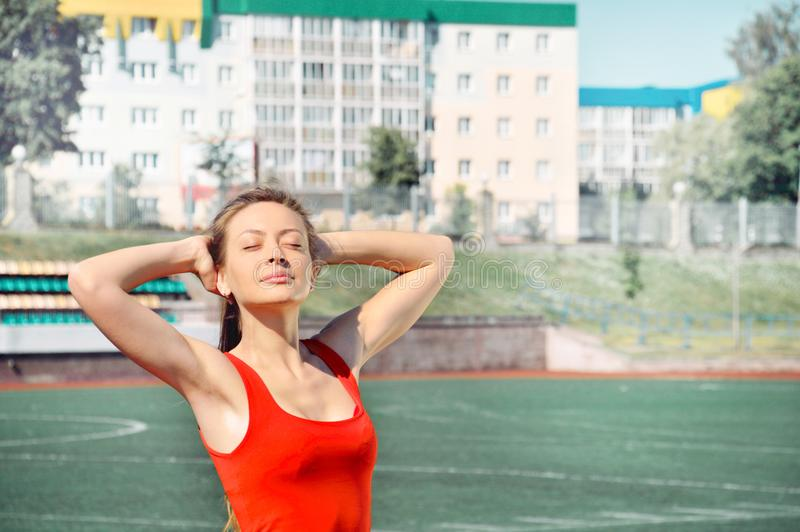 Close up portrait of young woman runner with hands behind head. Beautiful smiling young athlete woman working out. Fitness concept stock images