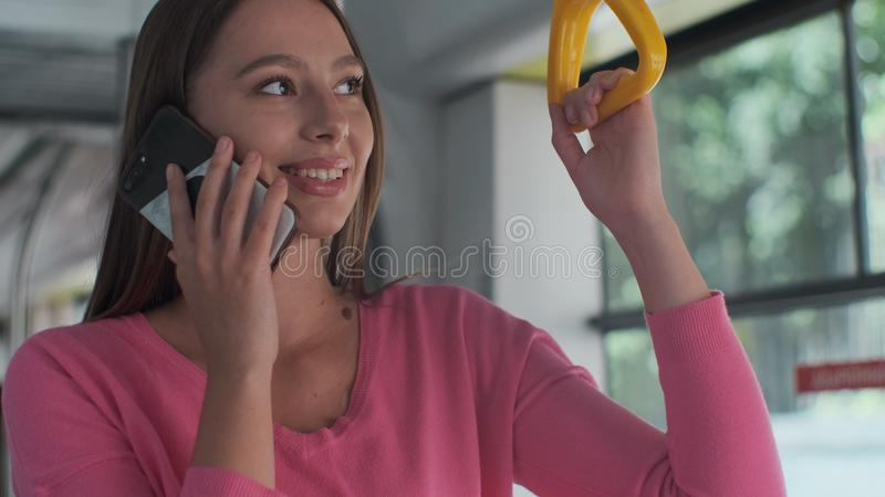 Close-up portrait of a young woman using smartphone while standing in the modern tram. Close-up portrait of a young woman using smartphone while standing in the stock image