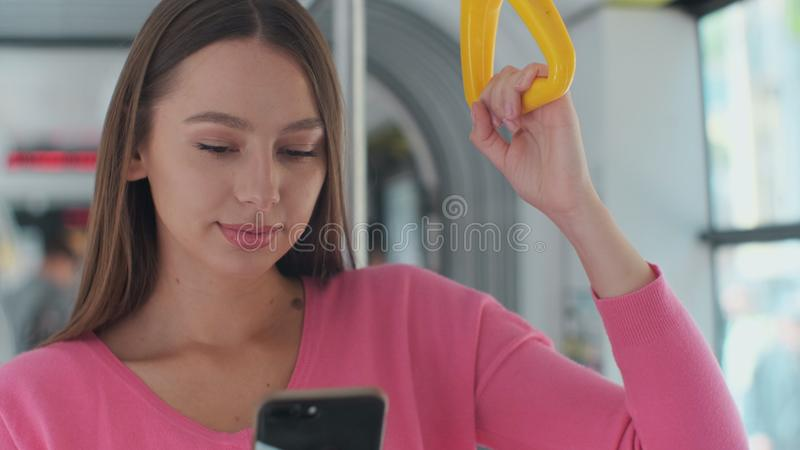 Close-up portrait of a young woman using smartphone while standing in the modern tram. Close-up portrait of a young woman using smartphone while standing in the royalty free stock photos