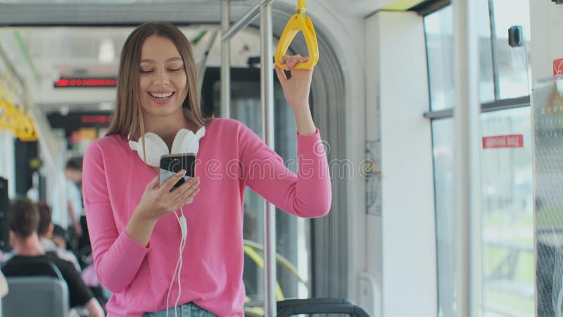 Close-up portrait of a young woman using smartphone while standing in the modern tram. Close-up portrait of a young woman using smartphone while standing in the stock photo