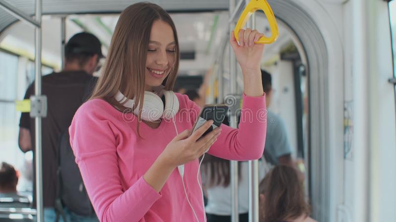 Close-up portrait of a young woman using smartphone while standing in the modern tram. Close-up portrait of a young woman using smartphone while standing in the royalty free stock photo