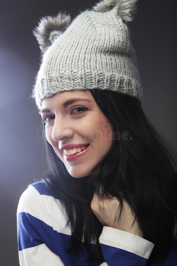 Close up portrait of young woman wearing funny hat. Over grey background royalty free stock photography
