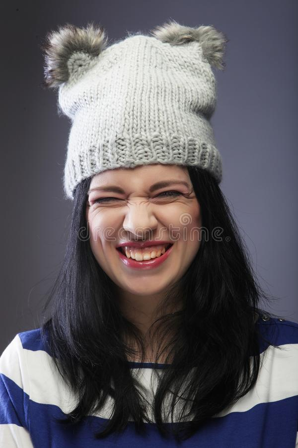Close up portrait of young woman wearing funny hat. Over grey background royalty free stock image