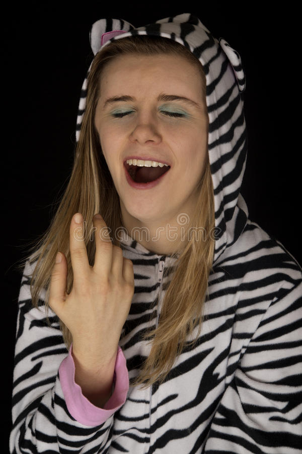 Close up portrait of a young woman yawning in cat pajamas. Close up portrait woman yawning cat pajamas stock images