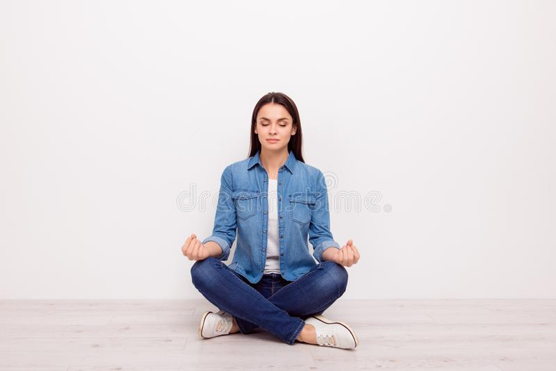 Close up portraitt of calm silent tranquile meditative lady with sign symbol om sitting in lotus position on the floor on. White background copy-space stock image