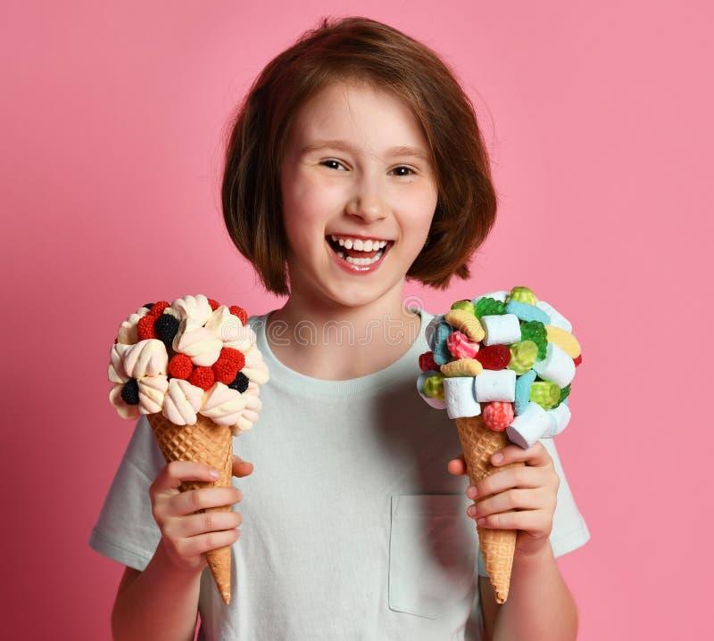 close-up Portret die van het gelukkige het lachen jonge geitje van het tienermeisje groot roomijs twee in wafelskegel houden met  stock afbeelding