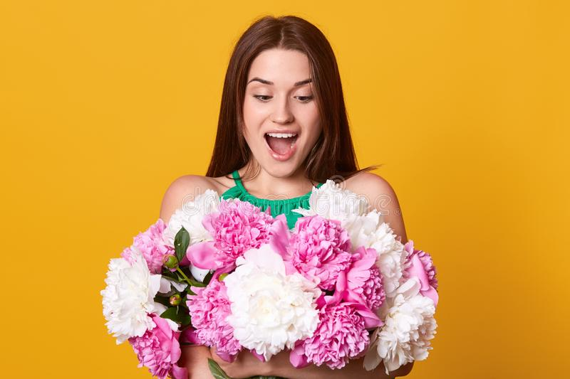 Close up portrtait of beautiful surprised romantic young woman, posing with open mouth, smiling girl holding bouquet of white and stock images