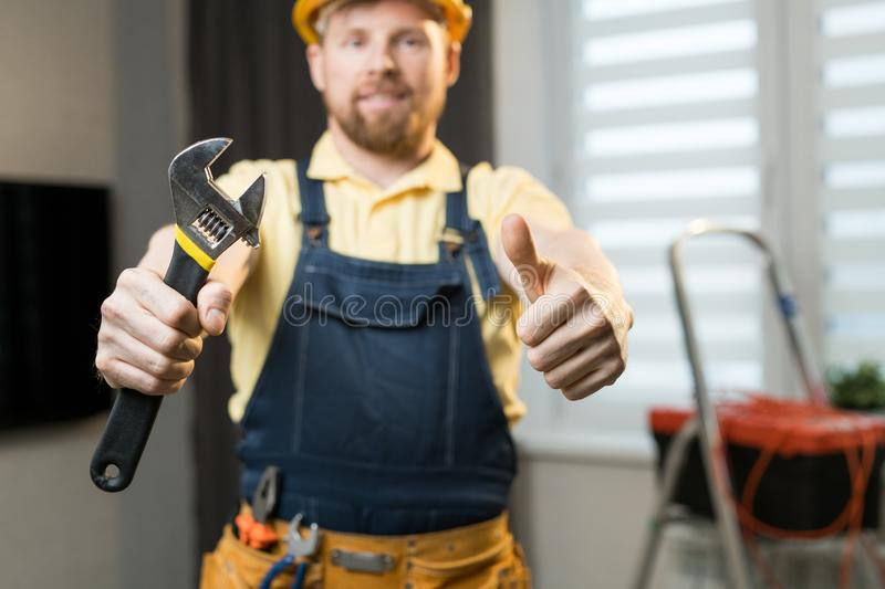 Positive handyman showing work tool. Close-up of positive young handyman showing thumb-up and holding work tool while standing in modern apartment royalty free stock photos