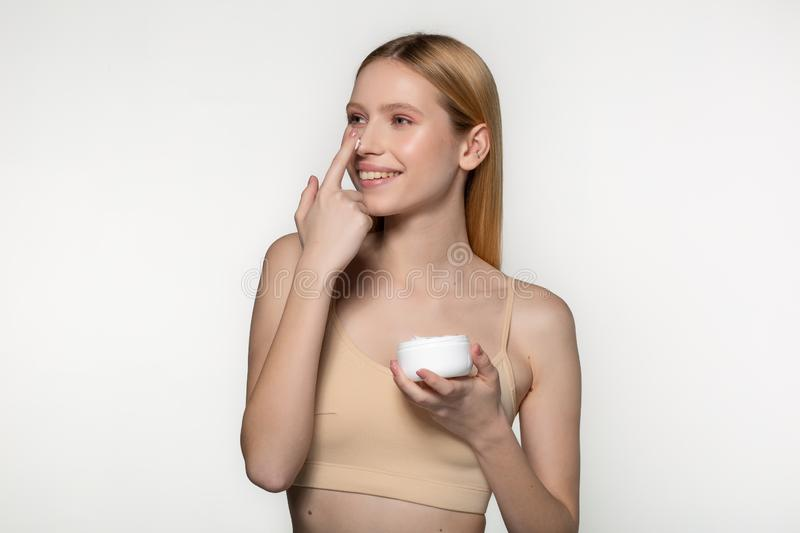 Close up of positive young woman with blonde hair standing with a jar of cream in her hand and smiling while putting stock image
