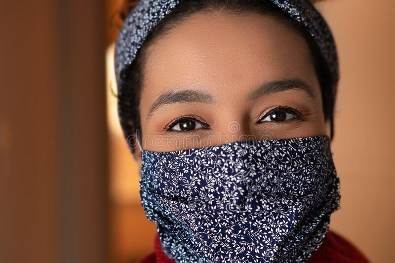 Close up of black woman with blue mask looking at camera. At apartment door entrance. Individuality, style, identity, royalty free stock images