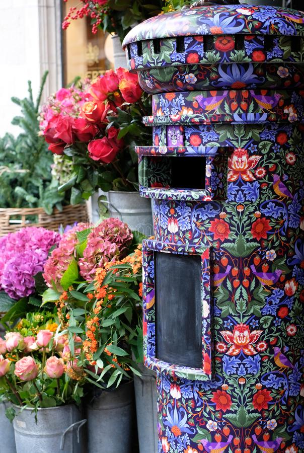 Close up of post box covered in Liberty print, located in the flower shop outside Liberty of London store. royalty free stock images