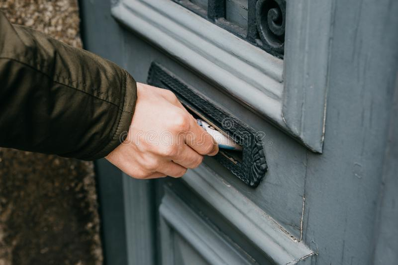 Close-up. The postman puts a letter or newspaper or magazine in the mailbox at the door of a residential building or a royalty free stock photo