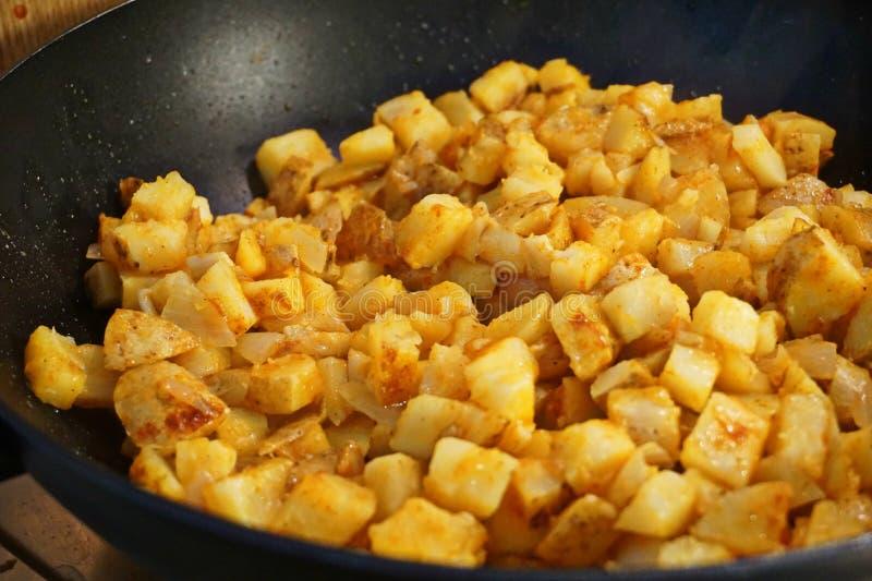 Potato hash frying in a frying pan stock image