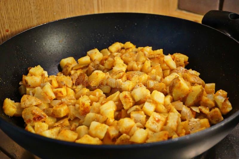 Potato hash frying in a frying pan royalty free stock photos