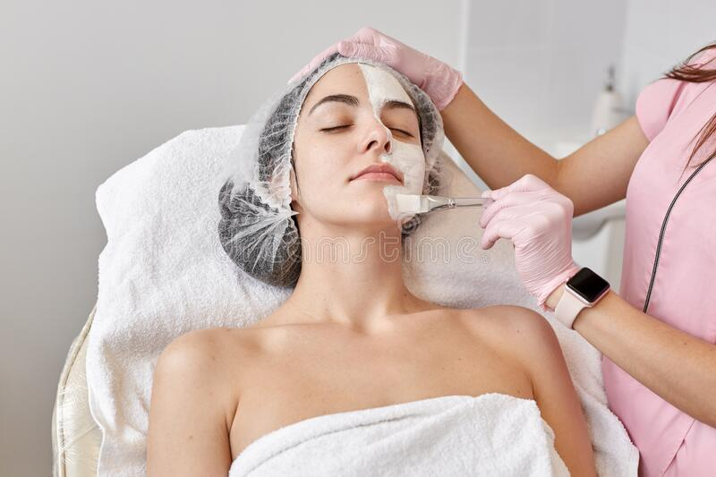 Close up potrait of hands of woman in spa salon, doctor cosmetologist applying healing cream with brush on her face, caucasian royalty free stock image