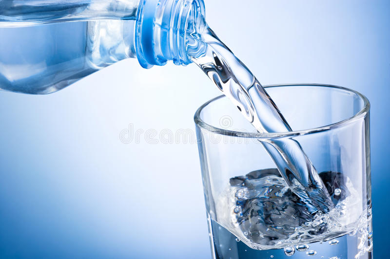 Close-up pouring water from bottle into glass on blue backgrou stock photos