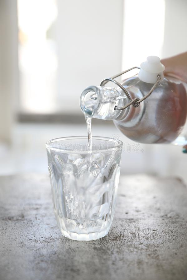 Close up pouring water to glass from the bottle on table in coffee shop royalty free stock photo