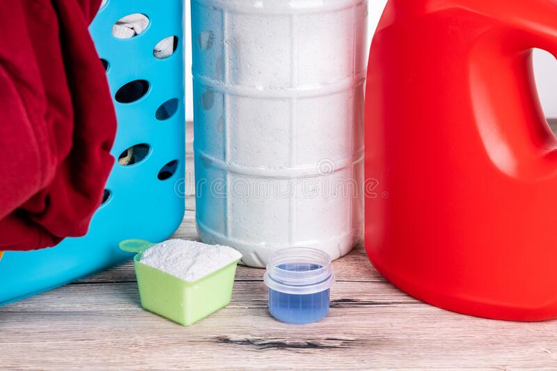 Close-up on powder and regular liquid laundry detergent on wooden surface royalty free stock photos
